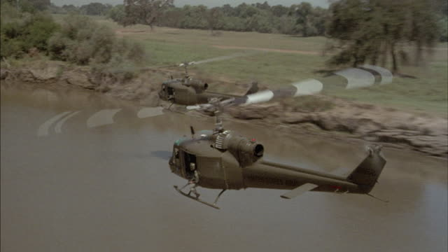 Two military helicopters that read United States Army, fly over a river in Vietnam.