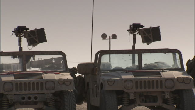 two military jeeps parked next to each other on unidentifiable desert no machine guns on gun mounts modern warfare war army equipment base camp not... - base camp stock videos & royalty-free footage