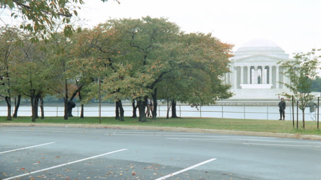 two military vehicles drive in a parking lot near the jefferson memorial in washington, dc. - jefferson memorial stock videos & royalty-free footage