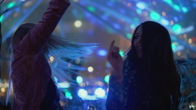 vídeos y material grabado en eventos de stock de slo mo. two millennial hipster women dance together at a popular music festival - club