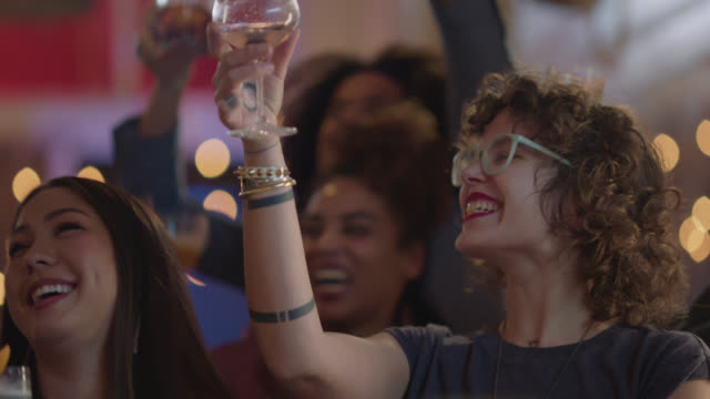 two millennial woman cheer and do a celebratory toast with a group of friends at a bar - straight hair stock videos & royalty-free footage