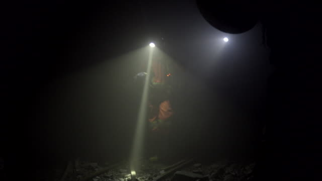 two miners with head lamps walk towards camera in mining tunnel - miner stock videos & royalty-free footage