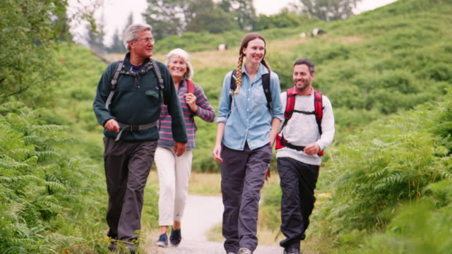 Two mixed age couples  walking on a countryside path during family camping adventure, Lake District, UK