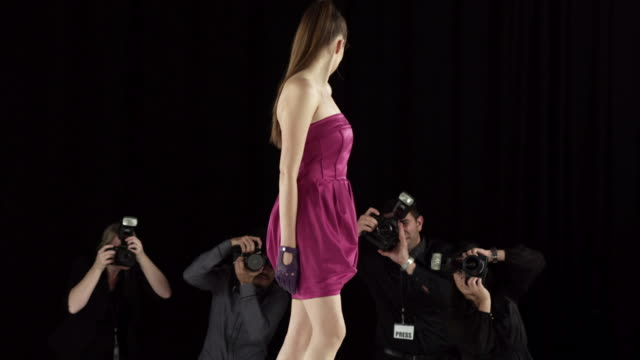 Two models on catwalk at fashion show with photographers