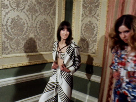 two models pose together one is wearing a striped catsuit with a bikini top the other a brightly patterned pantaloon jumpsuit 1969 - 1960 1969 video stock e b–roll