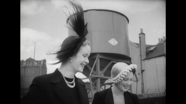 two models pose wearing black and white hats decorated with feathers and bobbles - cappello video stock e b–roll