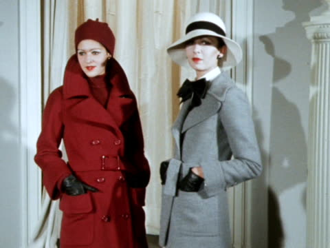 Two models wear a coat and trouser suit designed by Ricchi