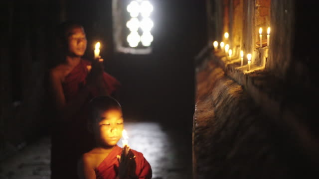 two monks praying with candle in the dark temple