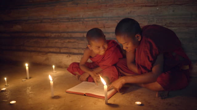 two monks reading book together in candle light