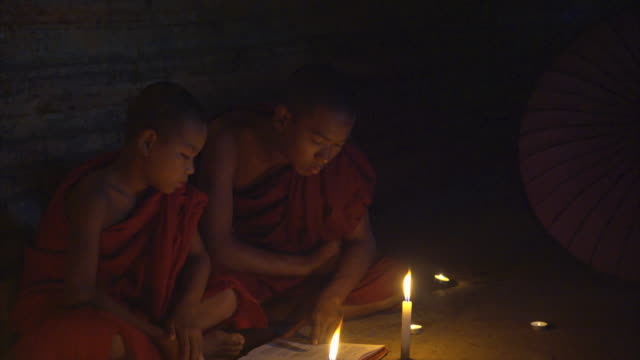 two monks reading book together in candle light - candlelight stock videos & royalty-free footage