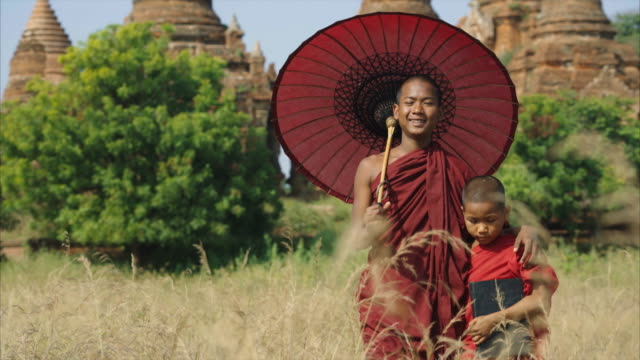 two monks walking in the field front of temple holding umbrella - myanmar stock-videos und b-roll-filmmaterial