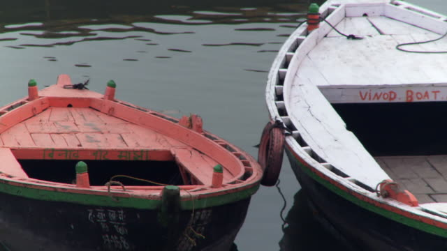 two moored boats floating by each other. - due oggetti video stock e b–roll
