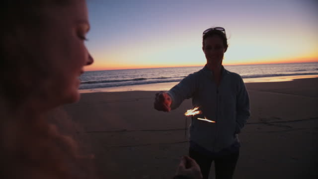 two mothers, a boy, and a girl light sparklers at sunset on the beach of bald head island on thanksgiving evening on a family vacation - house rental stock videos & royalty-free footage