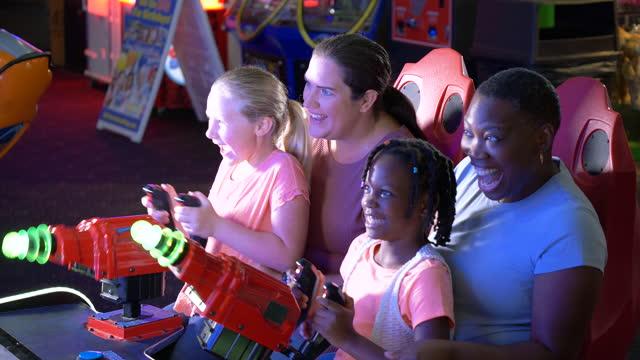 stockvideo's en b-roll-footage met twee moeders, dochters die spel arcadespel spelen - 35 39 years