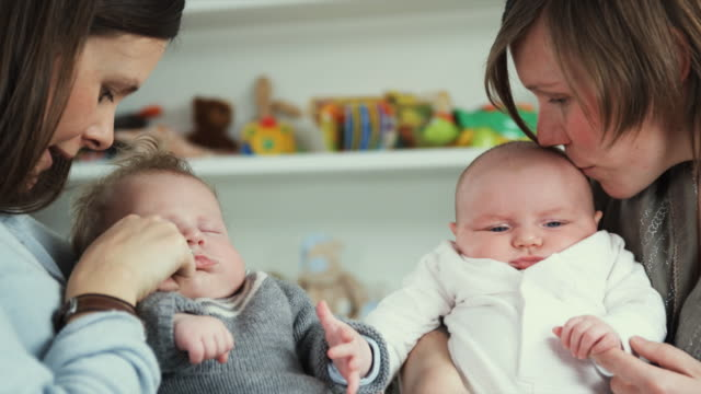 vídeos de stock e filmes b-roll de cu two mothers holding babies (2-5 months), standing in nursery, brussels, belgium - 2 5 meses