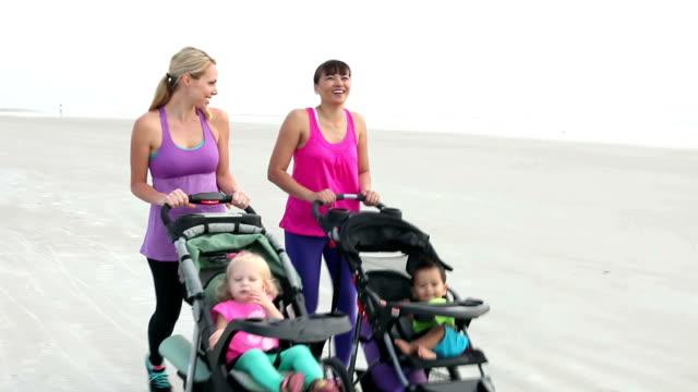 Zwei Mütter am Strand wandern mit Kinderwagen