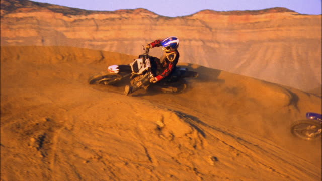 SM HA WS Two motocross riders driving on dirt hill in desert / Colorado, USA