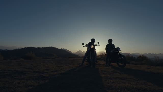 two motorcycle riders in backlight during sunset - in silhouette stock videos & royalty-free footage