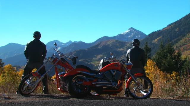 vidéos et rushes de two motorcyclists making a pit stop - motard