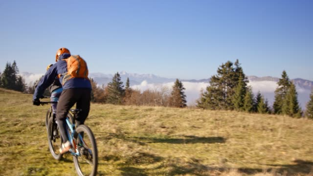 two mountain bikers descending the mountain riding across a meadow in sunshine - wide shot stock videos & royalty-free footage