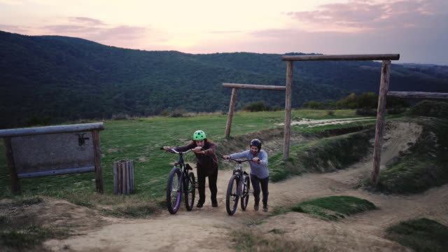 Two mountain bikers pushing their bicycles uphill at sunset.