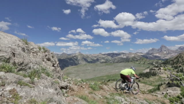 Two mountain bikers ride down a rocky path at Grand Targhee in Wyoming and jump off a small rock