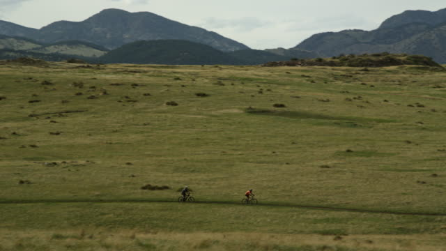 Two mountain bikers ride down hill across a grass field with mountains in the background