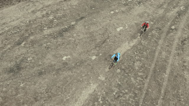 AERIAL Two mountain bikers riding across a mountain clearing