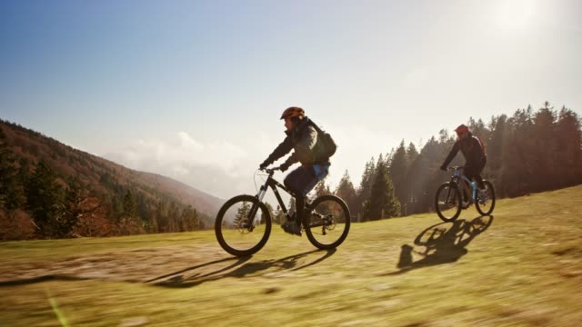 ts two mountain bikers riding fast on a mountain path in sunshine - wide shot stock videos & royalty-free footage
