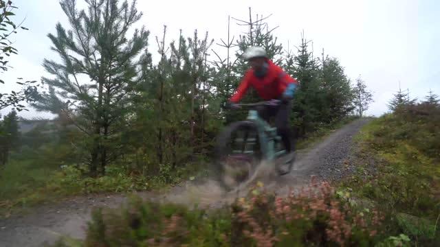 vídeos y material grabado en eventos de stock de dos ciclistas de montaña acelerando a través del agua en un sendero para bicicletas de montaña - deporte de invierno