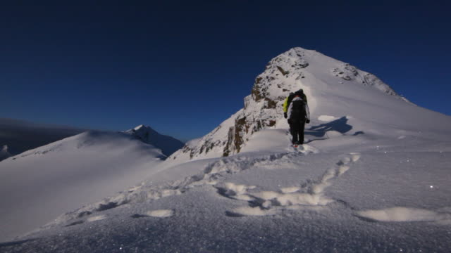 Two mountain climbers ascend a snow and ice covered mountain in the Austrian Alps.