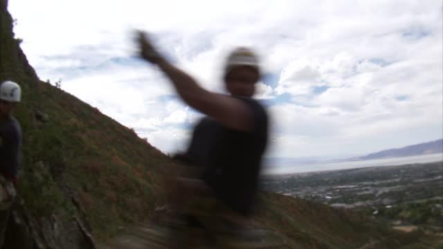 vídeos de stock, filmes e b-roll de ms two mountain climbers jumping over camera / provo, utah, usa - corda de escalada