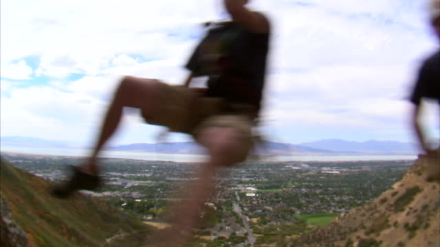vídeos de stock e filmes b-roll de ms two mountain climbers jumping over camera / provo, utah, usa - provo