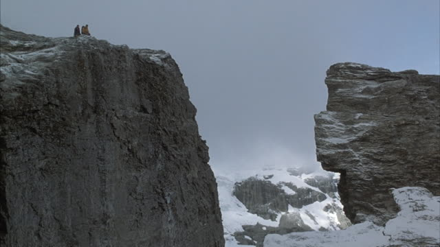 two mountain climbers look into the distance from a high mountain ledge. - crevasse stock videos & royalty-free footage