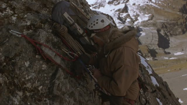 two mountain climbers prepare to climb higher up a vertical rock face. - 高い点の映像素材/bロール