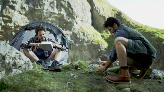 vídeos de stock, filmes e b-roll de two mountaineers at their base camp in rugged terrain. - amizade masculina