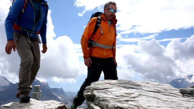 Zwei Bergsteiger Klettern auf high ridge Wappen