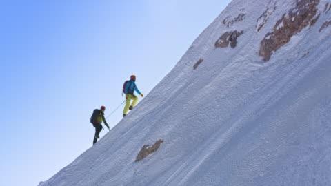 vídeos y material grabado en eventos de stock de dos montañeros subiendo por la empinada pendiente nevada - cuerda