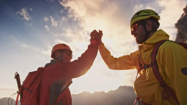 two mountaineers doing a handshake on mountain top at sunset - two people stock videos & royalty-free footage