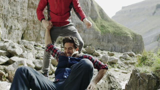 stockvideo's en b-roll-footage met two mountaineers helping each other during a tough climb in rugged terrain. - oppakken