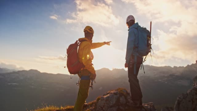 two mountaineers reaching mountain top and shaking hands at sunset - climbing rope stock videos & royalty-free footage