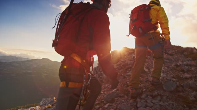 slo mo two mountaineers reaching the mountain top at sunset - sports equipment stock videos & royalty-free footage
