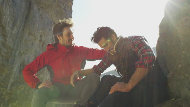 Two mountaineers resting during a climb in rugged terrain