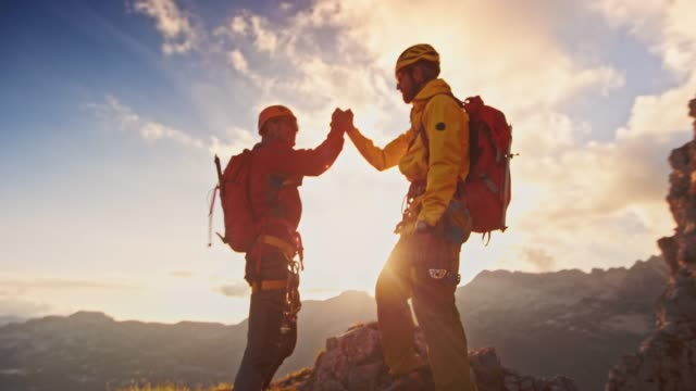 slo-mo-zwei bergsteiger, die hände schütteln, wie sie den gipfel bei sonnenuntergang erreichen - abenteuer stock-videos und b-roll-filmmaterial