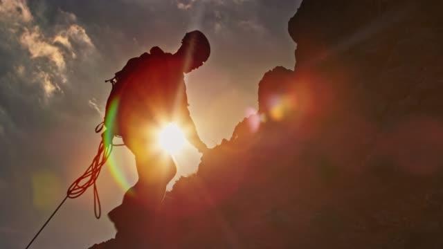 vídeos de stock, filmes e b-roll de dois alpinistas subindo a montanha em chamas do sol - parélio