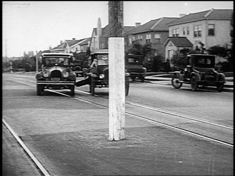 b/w 1926 two moving cars with man (harry langdon) stretched between them approaching pole in road - 1926 stock-videos und b-roll-filmmaterial