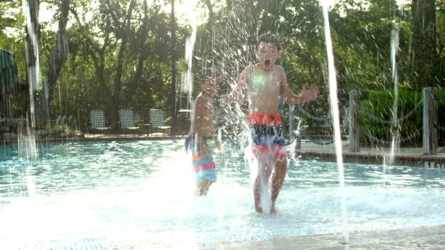 two multi-ethnic boys playing in water fountains - 8 9 years stock videos & royalty-free footage