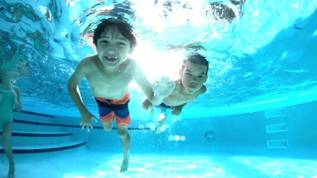 two multi-ethnic boys swimming underwater in pool - surfacing stock videos & royalty-free footage