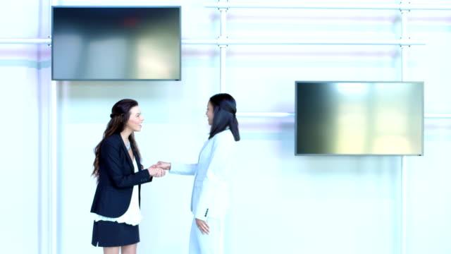 due imprenditrici multietniche si incontrano, si stringono la mano, parlano - divisione video stock e b–roll