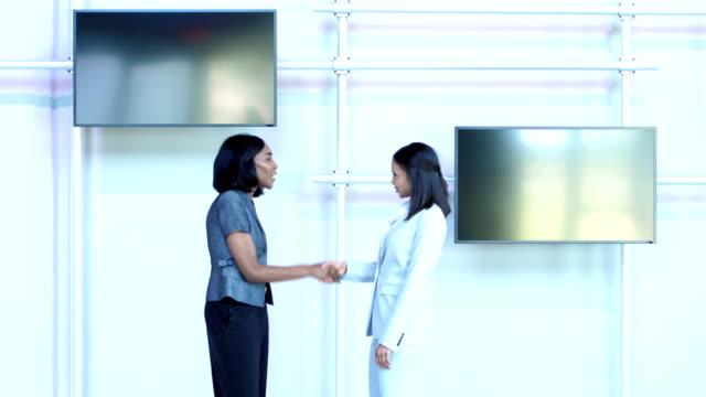vidéos et rushes de deux femmes d'affaires et multiethniques, rencontrer, serrent la main, parler - profil